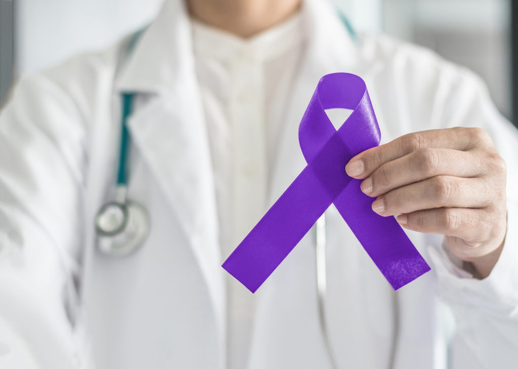 Purple violet ribbon symbolic bow color on doctor's hand support for Hodgkin's lymphoma and testicular cancer awareness